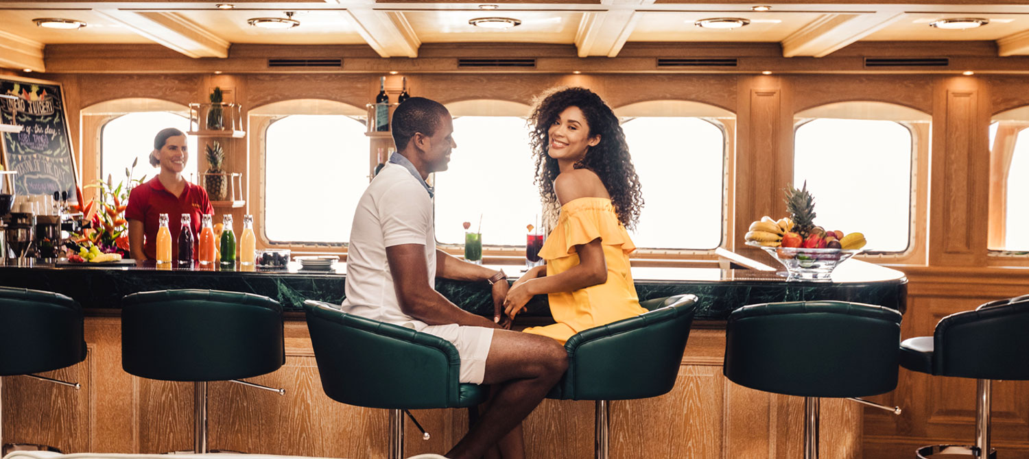 Man and woman sitting at the bar on NERO yacht with bartender off to the corner smiling at couple.